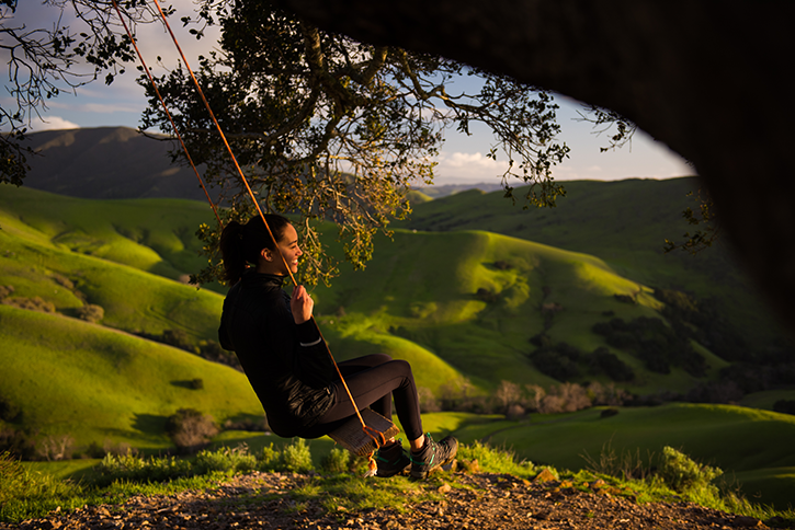 At sunset, a Cal Poly student enjoys a swing on an oak tree while looking at the rolling green hills of PolyCanyon.