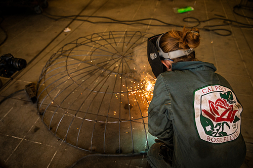 A student welds together part of the frame for the 2019 Cal Poly Rose Float.
